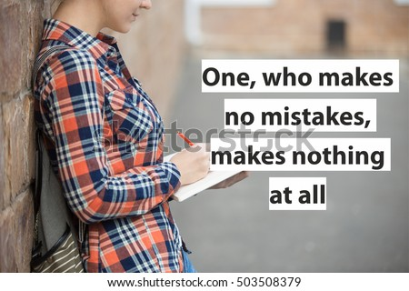 """Student girl in a yard against the brick wall writing in an open notebook with a pen. Back to school concept photo, closesup. Motivational text """"One, who makes no mistakes, makes nothing at all"""""""