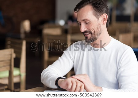 Smiling bearded man checking time in cafe #503542369