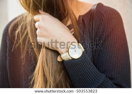 fall outfit fashion details, young woman holding her hair, wearing a beautiful white and golden watch. graded in warm colors.   Royalty-Free Stock Photo #503553823