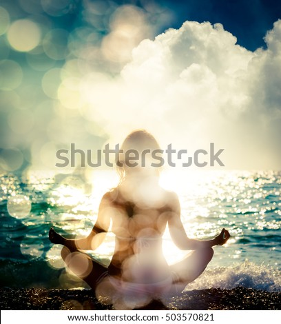 Woman Practicing Yoga by the Sea. Silhouette of a Slim Girl. Nature Background with Sunlight Bokeh. Meditation, Spiritual and Soul Concept. Healthy Lifestyle. Double Exposure Filtered Photo. #503570821