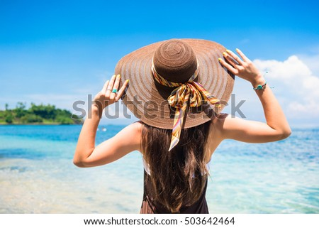 Woman in summer vacation wearing straw hat and beach dress enjoying the view at the ocean #503642464