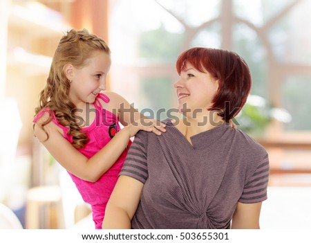 Happy family of two people,an adult mother, her beloved daughter 7 years. Daughter gently hugs the mother's neck. Close-up.In a room with a large semi-circular window. #503655301