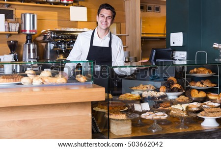 Happy man selling tarts and sweet pastry in coffee-house #503662042