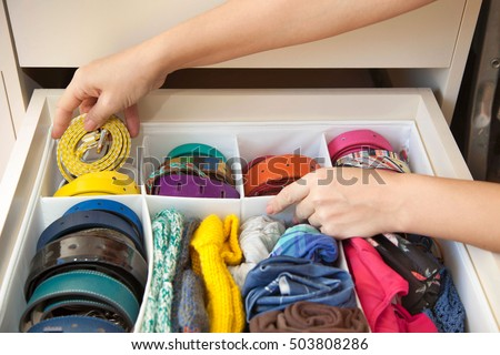 The woman pulls out a strap from a drawer of the wardrobe. Drawer with straps and belts. #503808286