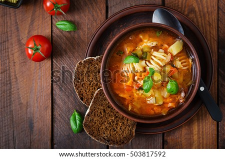 Minestrone, italian vegetable soup with pasta on wooden table. Top view #503817592