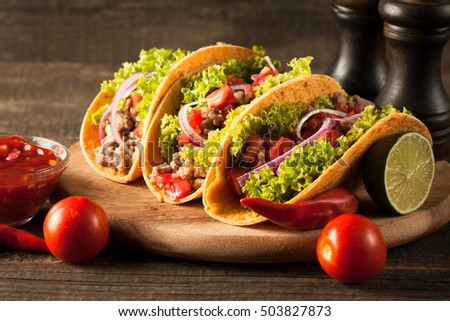 Photo of Mexican tacos with ground beef, onion, tomatoes, chili, red sauce, lettuce and lime on wooden background. Spicy and fast food concept. #503827873