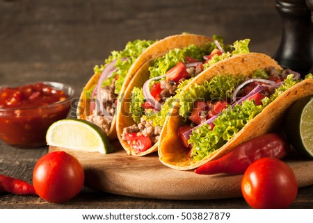 Photo of Mexican tacos with ground beef, onion, tomatoes, chili, red sauce, lettuce and lime on wooden background. Spicy and fast food concept. #503827879