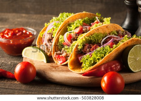 Photo of Mexican tacos with ground beef, onion, tomatoes, chili, red sauce, lettuce and lime on wooden background. Spicy and fast food concept. #503828008