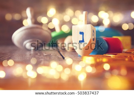 Image of jewish holiday Hanukkah with wooden dreidels colection (spinning top) and chocolate coins on the table. Glitter overlay
