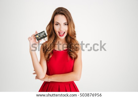 Cheerful young woman in red dress holding bank card isolated on a white background #503876956