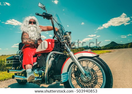 Sunburned Santa biker riding motorcycle on summer vacations