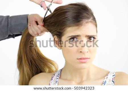 young woman worried about cutting her long hair at the hairdresser #503942323