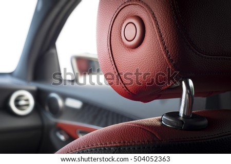 Car headrest seat in modern luxury comfortable car with red perforated leather Royalty-Free Stock Photo #504052363