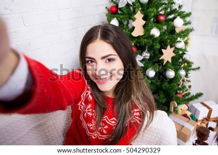 christmas concept - young woman taking selfie photo near decorated christmas tree