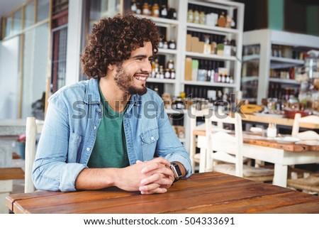 Man sitting and smiling in cafeteria #504333691