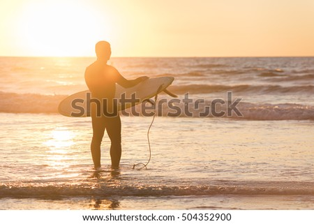 Silhouette of a surfer in front of sun with board during sunset in San Diego, California, with creative flare #504352900