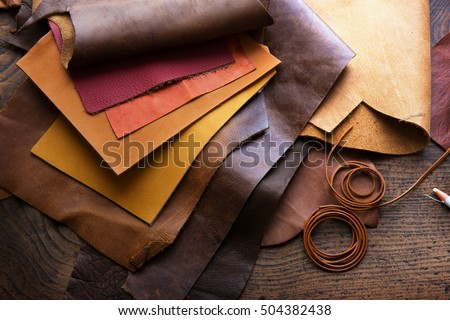 Leather craft or leather working. Selected pieces of beautifully colored or tanned leather on leather craftman's work desk. Royalty-Free Stock Photo #504382438