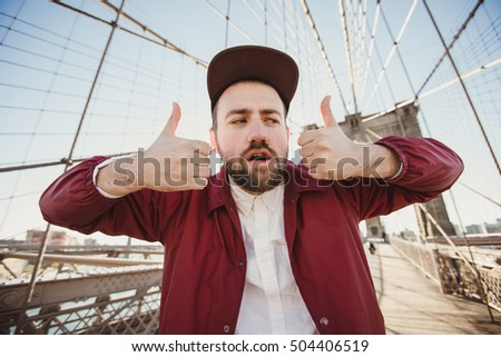 Handsome hipster guy taking selfie portrait on Brooklyn Bridge, New York. Cute bearded student takes funny picture with thumbs up for travel blog. #504406519
