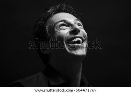 Isolated caucasian man face laughing . Black background, black and white picture
