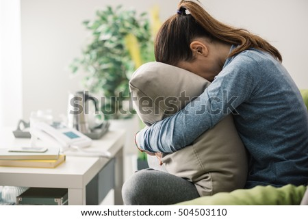 Unhappy lonely depressed woman at home, she is sitting on the couch and hiding her face on a pillow, depression concept Royalty-Free Stock Photo #504503110