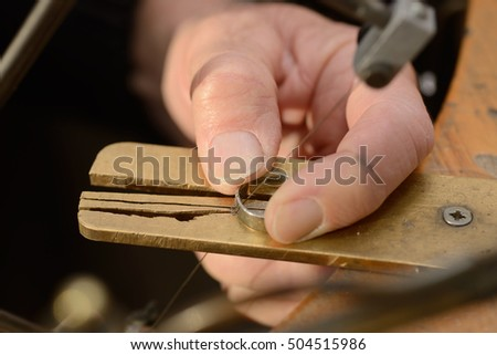 A goldsmith uses a fine saw to cut a small section from a gold ring for resizing