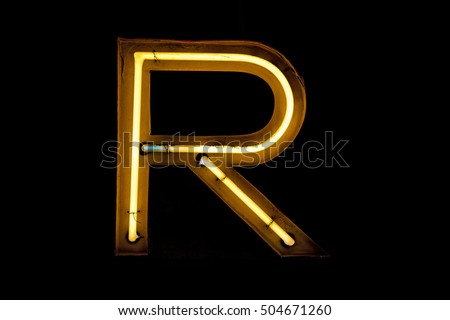 Vintage neon capital letter R lighted up. On the black background.