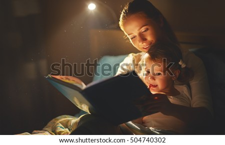 mother and child girl reading a book in bed before going to sleep #504740302