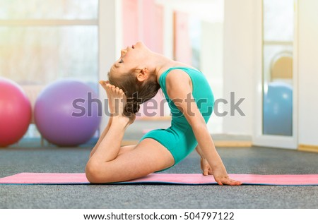 Flexible little girl gymnast doing acrobatic exercise in gym. Sport, training, fitness, yoga, active lifestyle concept