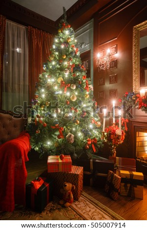 Christmas evening by candlelight. classic apartments with a white fireplace, decorated tree, sofa, large windows and chandelier. #505007914
