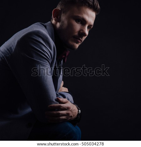 Side view of male in gray jacket with butterfly that looking forward on black background #505034278
