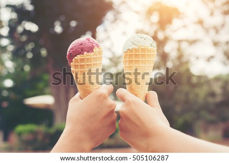 Woman's hands holding melting ice cream waffle cone in hands on summer light nature background #505106287
