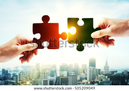 Hands putting puzzle piece together on bright city background with sunlight. Teamwork concept #505209049