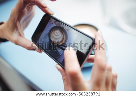 Woman taking photo of a coffee from mobile phone in office #505238791