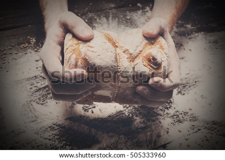 Warm fresh bread. Baking and cooking concept background. Hands of baker carefully hold loaf on rustic wooden table, sprinkled with flour. Stained dirty hands. Soft toning #505333960