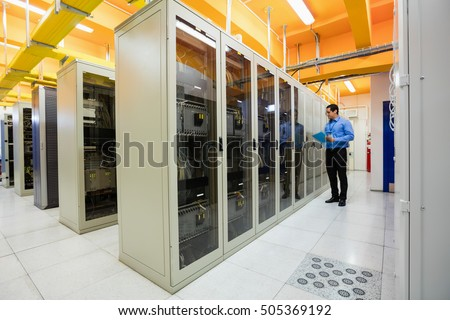 Technician preparing check list in server room Royalty-Free Stock Photo #505369192