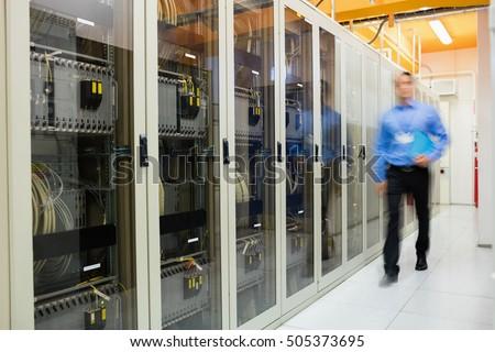 Technician walking in corridor of server room Royalty-Free Stock Photo #505373695