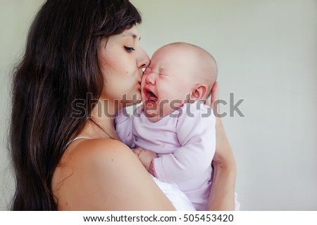 The little two-month girl cries at the mother on hands. Mother and daughter #505453420