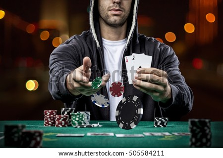 Poker player showing a pair of aces, on a bokeh lights background. Royalty-Free Stock Photo #505584211