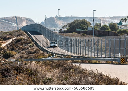 San Diego, California and Tijuana, Mexico international border wall with border patrol vehicle.  #505586683
