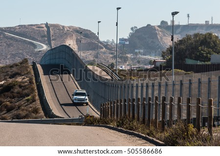 Border Patrol vehicle patrolling along the fence of the international border between San Diego, California and Tijuana, Mexico #505586686