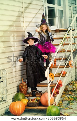 Happy children in a costumes of witches and wizards celebrating halloween. Trick or treat. Halloween party. #505693954