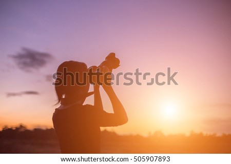 silhouette portrait of a young woman photographing a beautiful nature at sunset on photo equipment #505907893