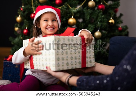 Happy little girl holding gift for Christmas. Soft focus, high ISO, grainy image.
