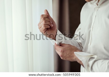 Businessman dresses white shirt, male hands closeup,groom getting ready in the morning before wedding ceremony #505949305