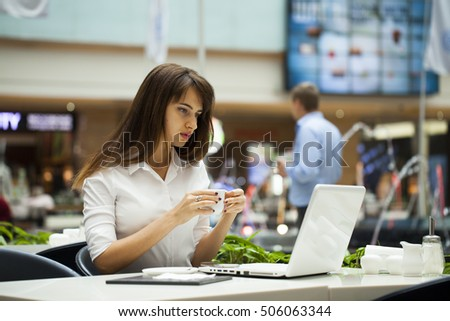 Young beautiful business woman drinking coffee while sitting in a restaurant #506063344