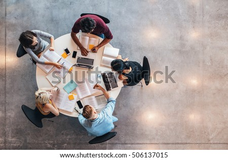 Top view of group of students sitting together at table. University students doing group study. Royalty-Free Stock Photo #506137015