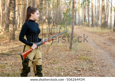 portrait Young beautiful woman hunter with a shotgun in the forest #506264434