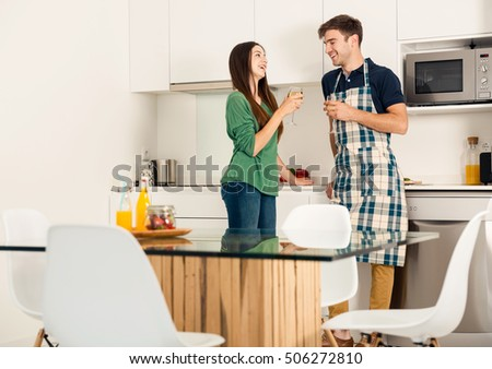 Young couple on the kitchen enjoying a  glass of white wine #506272810