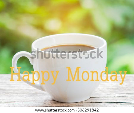 "word ""Happy Monday"" over image of a cup of coffee on wooden table against burred nature background"