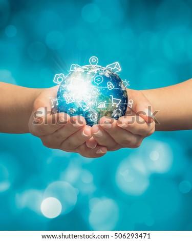 female hands holding globe and media icons flying around globe #506293471